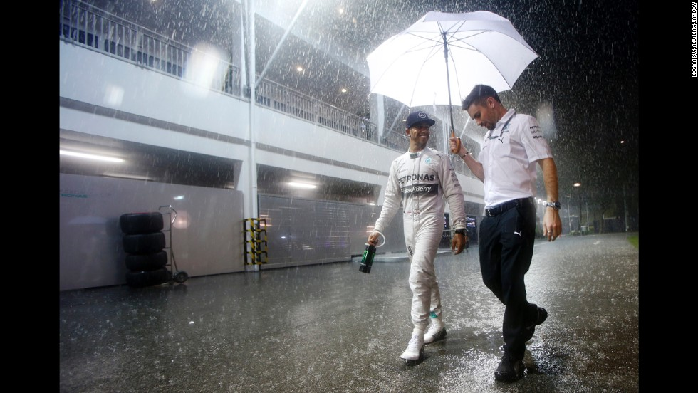 After winning the pole for the Singapore Grand Prix, Formula One driver Lewis Hamilton smiles as he walks with his assistant on Saturday, September 20. Hamilton would go on to win the race the next day and move to the top of the drivers' standings.