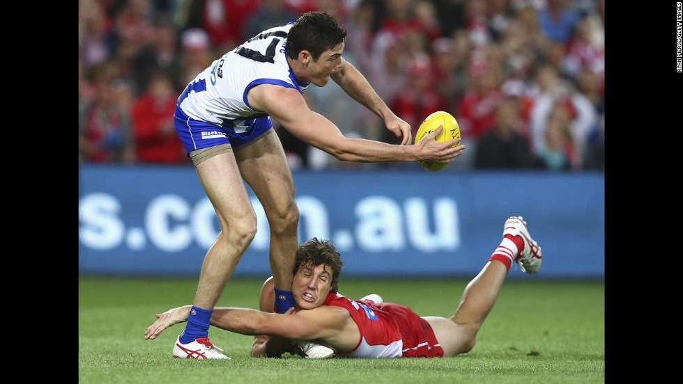 Kurt Tippett of the Sydney Swans tackles Nathan Grima of the North Melbourne Kangaroos during one of the Australian Football League's preliminary finals on Friday, September 19. Sydney won and advanced to the grand final against Hawthorn.