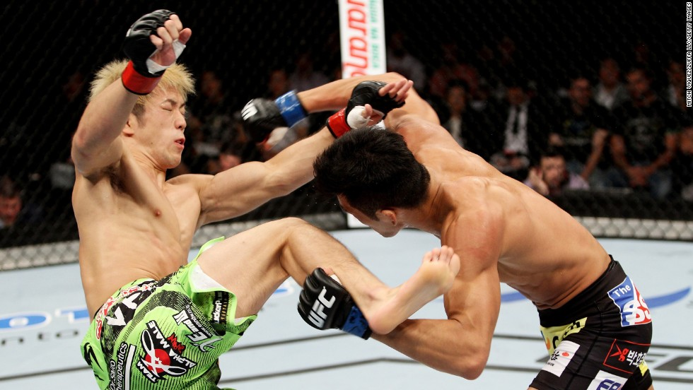 Kyung Ho Kang, right, goes for a takedown on Michinori Tanaka during their bantamweight bout Saturday, September 20, at UFC Fight Night in Saitama, Japan. Kang won by split decision.