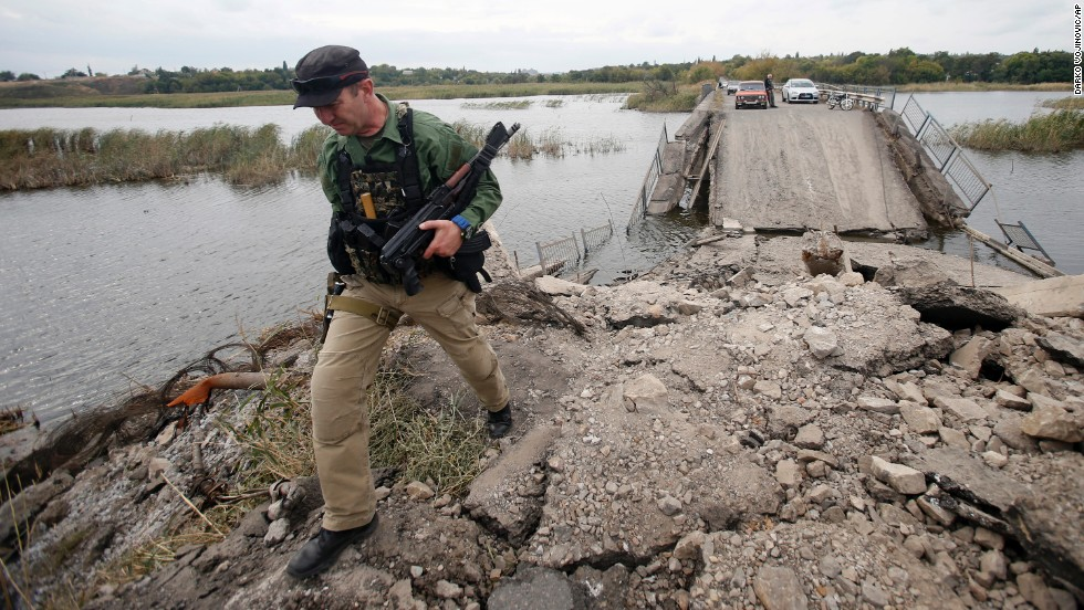 A pro-Russian rebel guards a destroyed bridge in Nyzhnya Krynka, Ukraine, on Tuesday, September 23.