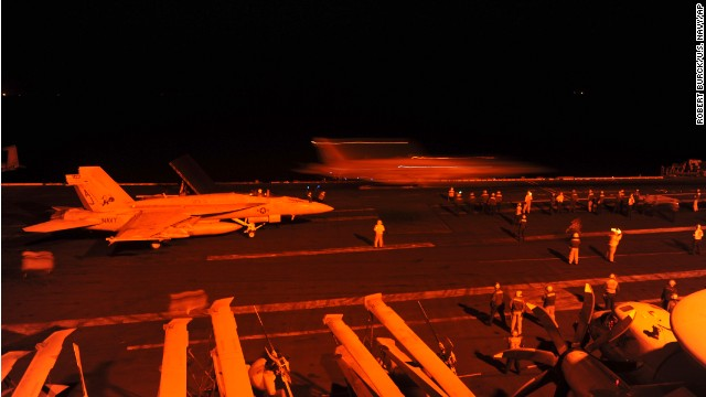 In this photo released by the U.S. Navy, A-18E Super Hornet, attached to Strike Fighter Squadron (VFA) 31, and an F/A-18F Super Hornet, attached to Strike Fighter Squadron (VFA) 213, prepare to launch from the flight deck of the aircraft carrier USS George H.W. Bush (CVN 77) to conduct strike missions against Islamic State group targets, in the Arabian Gulf, Tuesday, Sept. 23, 2014.