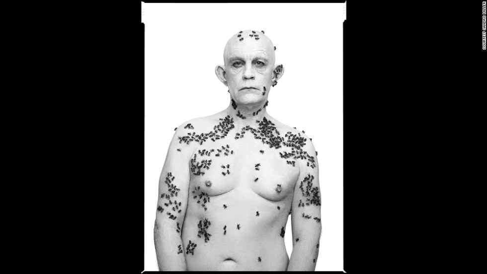 "Malkovich, covered in bees, re-creates the ""Ronald Fischer, Beekeeper"" photo taken by Richard Avedon in 1981."