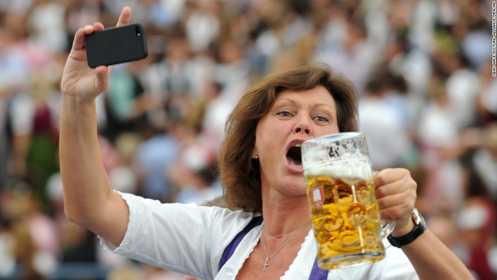 German politician Ilse Aigner holds her phone and a mug of beer Saturday, September 20, as she celebrates the opening day of Oktoberfest in Munich, Germany.