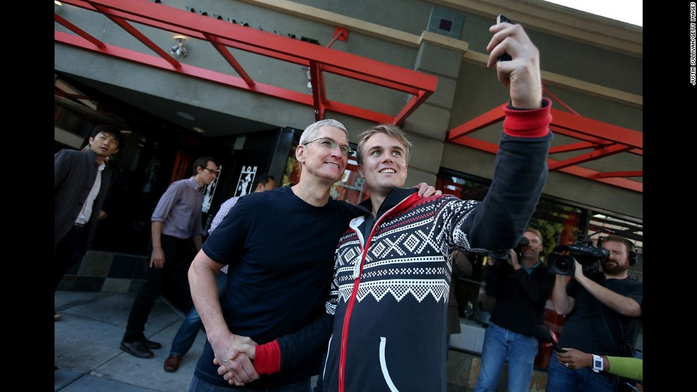 Apple CEO Tim Cook, left, shakes hands with a man waiting in line to buy the new iPhone 6 on Friday, September 19, in Palo Alto, California.