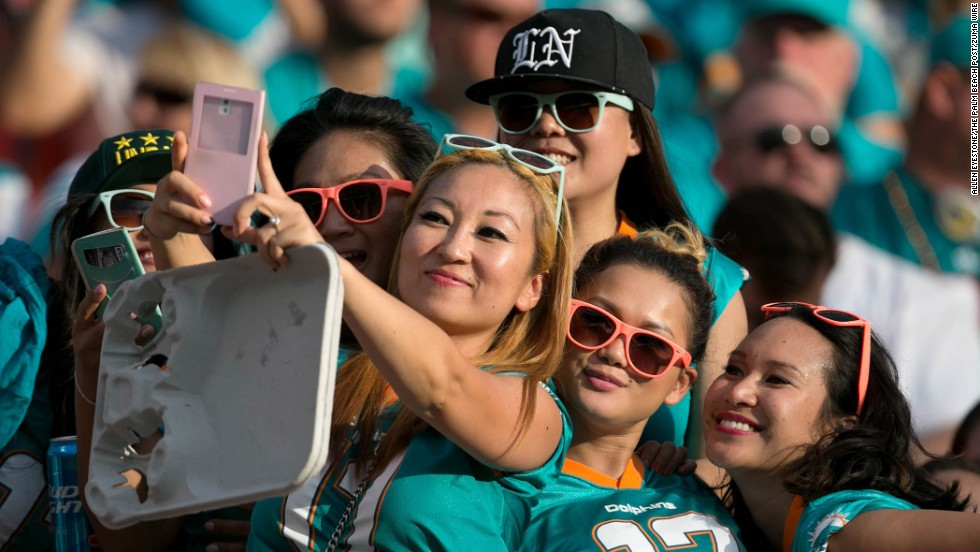 Fans of the NFL's Miami Dolphins pose for a selfie during the third quarter of the team's home game against the Kansas City Chiefs on Sunday, September 21.