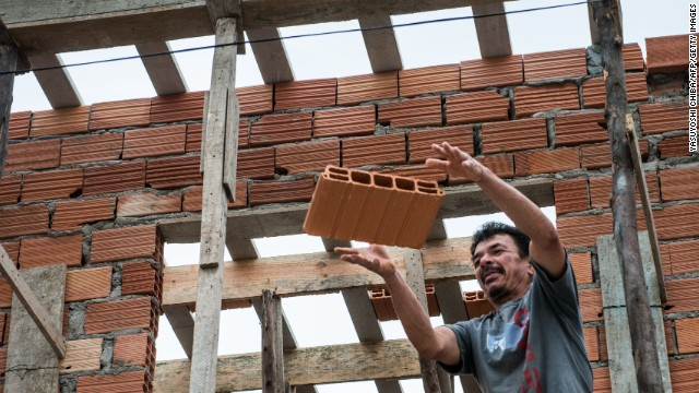 Caption:A bricklayer works in a house in Uniao de Vila Nova, recently converted in the framework of a favela upgrading project by the Sao Paulo state housing agency CDHU, in eastern Sao Paulo, Brazil on August 28, 2012. Sao Paulo state has an annual housing budget of $1.1 billion, 43 percent of which is spent on building new homes or upgrading existing ones for favela residents, according to CDHU. The Sao Paulo metropilitan area alone is home to 20 million people, roughly 10 percent of whom live in favelas and illegal settlements. AFP PHOTO/Yasuyoshi CHIBA (Photo credit should read YASUYOSHI CHIBA/AFP/Getty Images)