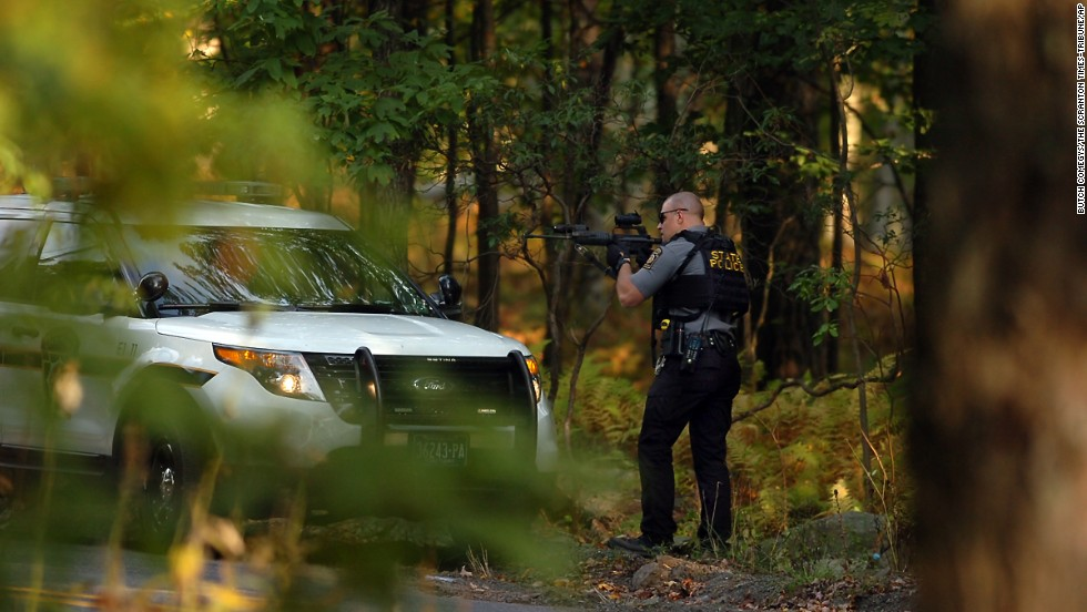 "A Pennsylvania state trooper draws his weapon in Price Township, Pennsylvania, during a manhunt for Eric Matthew Frein on Sunday, September 21. Frein <a href=""http://www.cnn.com/2014/09/22/justice/pennsylvania-suspected-cop-killer/index.html"">is wanted</a> for the shootings of two state police officers, one of whom died."