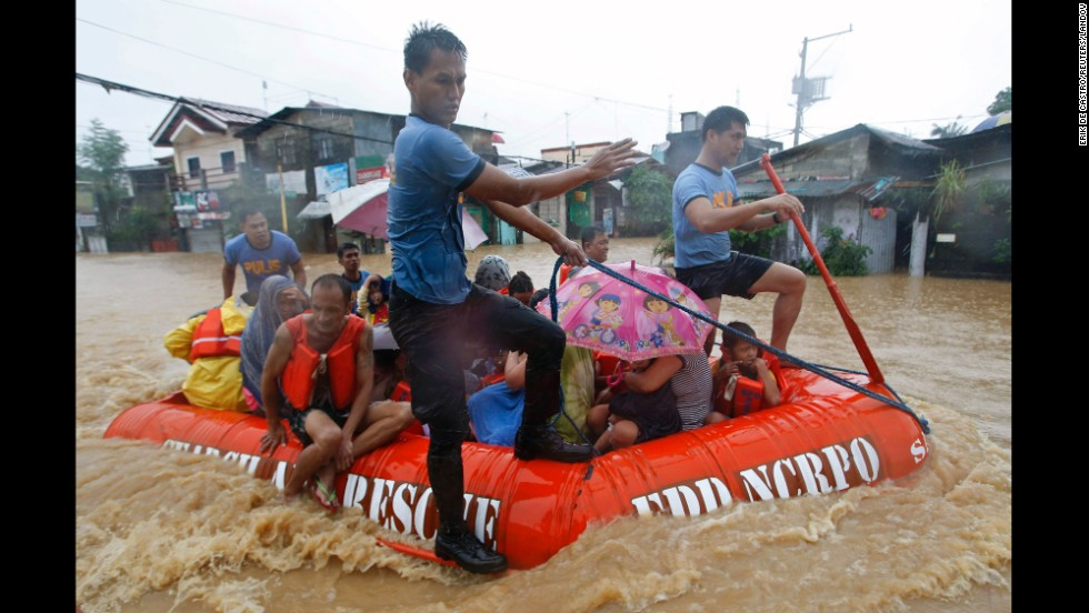 Flood victims ride in a rescue boat after their homes were swamped in Manila, Philippines, on Friday, September 19. Heavy rain in the capital city caused flooding in many areas and led to the closing of schools, government offices and financial markets.