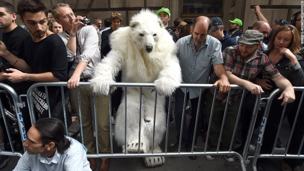 "A man dressed as a polar bear climbs a barricade Monday, September 22, as protesters took part in the ""Flood Wall Street"" demonstrations that preceded the U.N. Climate Summit in New York."