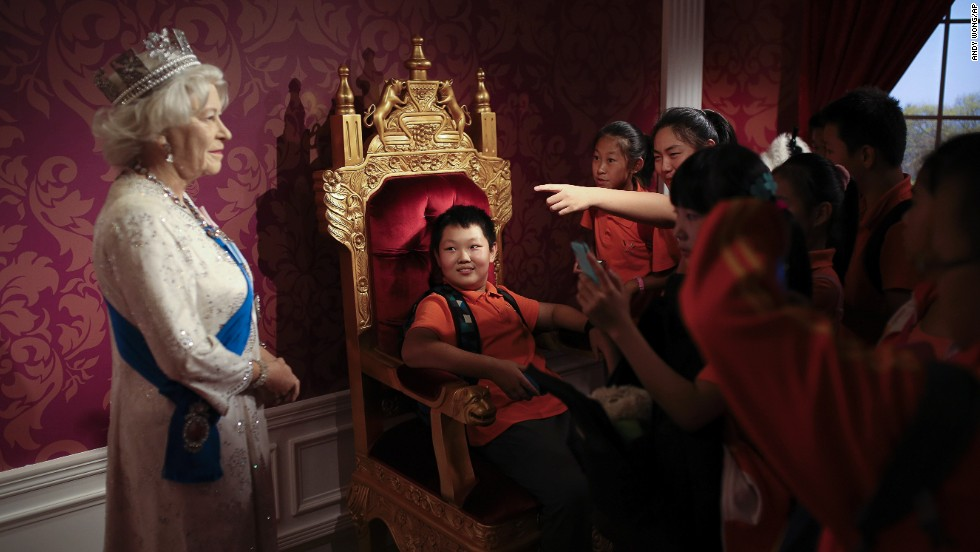 A student, sitting on a mock-up of a royal throne, looks at a wax figure of Britain's Queen Elizabeth II while other students take photos Friday, September 19, at the Madame Tussauds museum in Beijing.