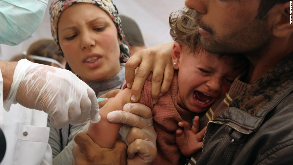 "A refugee girl is vaccinated shortly after she and her parents crossed into Suruc, Turkey, on Wednesday, September 24. Because of the militant group ISIS, <a href=""http://www.cnn.com/2013/03/05/world/gallery/syrian-refugees/index.html"">as many as 200,000 people have fled</a> the area surrounding the Syrian city of Kobani, also known as Ayn al-Arab, the Syrian Observatory for Human Rights said Monday, September 22."