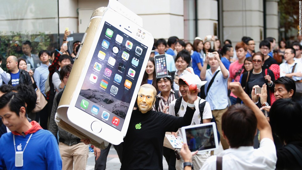 A man wearing a mask of Apple co-founder Steve Jobs holds a cardboard cutout of Apple's new iPhone 6 as he walks into an Apple Store in Tokyo on Friday, September 19.