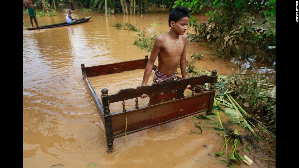 A boy carries a bed frame through floodwaters in the Indian village of Krishnai on Wednesday, September 24. Landslides and flash floods triggered by two days of heavy rain killed dozens of people in India's remote northeast.