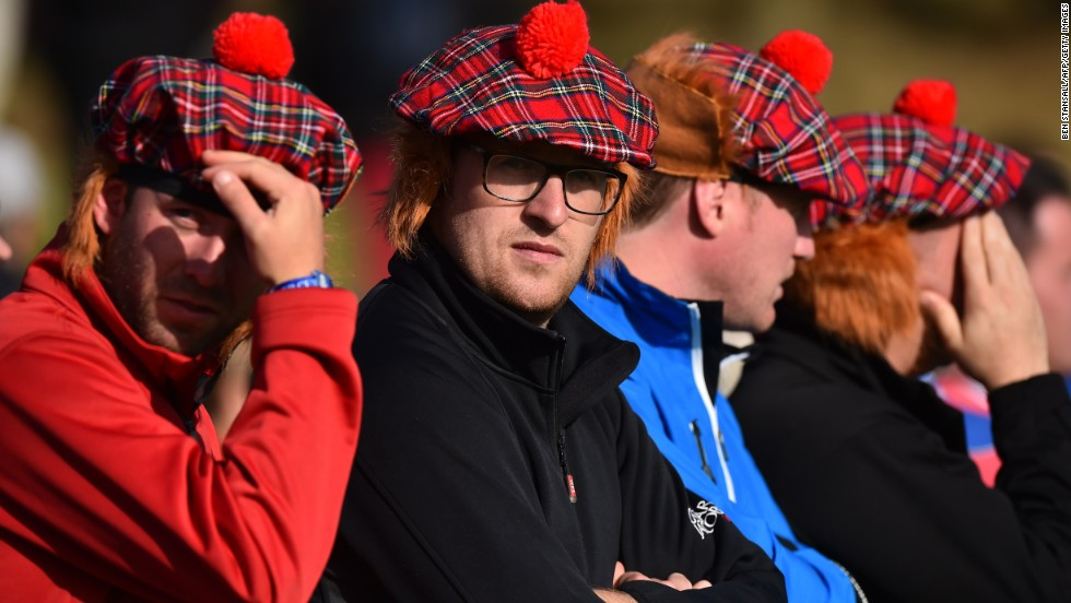 Spectators wearing Tartan caps complete with ginger wigs watch play during day one at Gleneagles.