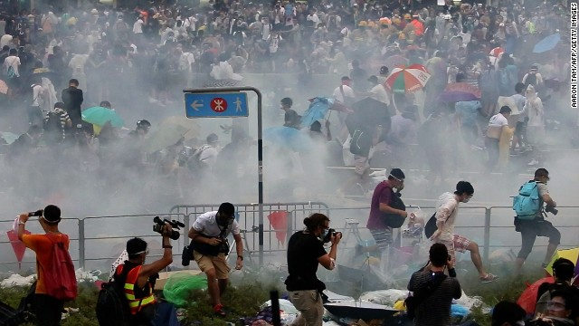 Caption:People disperse after police fired tear gas upon pro-democracy demonstrators near the Hong Kong government headquarters on September 28, 2014. Police fired tear gas as tens of thousands of pro-democracy demonstrators brought parts of central Hong Kong to a standstill on September 28, in a dramatic escalation of protests that have gripped the semi-autonomous Chinese city for days. AFP PHOTO / AARON TAM (Photo credit should read aaron tam/AFP/Getty Images)