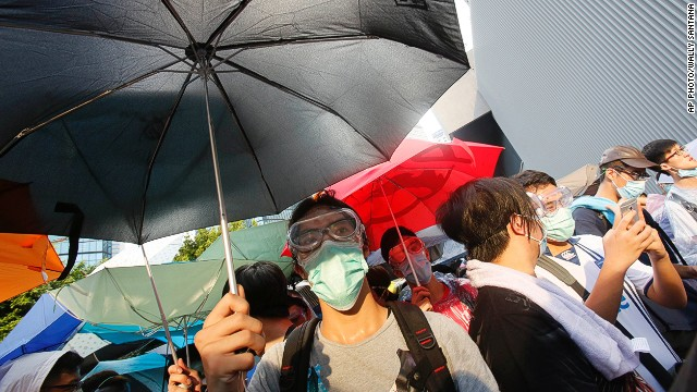 A student protester uses an umbrella to block pepper spray from riot police as thousands of protesters surround the government headquarters in Hong Kong, Sunday, Sept. 28, 2014. Hong Kong police used tear gas on Sunday and warned of further measures as they tried to clear thousands of pro-democracy protesters gathered outside government headquarters in a challenge to Beijing over its decision to restrict democratic reforms for the city. (AP Photo/Wally Santana)