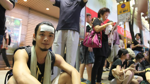 "Chung, 30, has been here 2-3 hours. Too many people in Admiralty, he says. He's an actor, here with a group of friends. Wearing cooling strip on his forehead (lots of people wearing these, pretty hot night) . Needs to work tomorrow. Haven't seen any police. ""Keep alert to everyone, everywhere. Undercover cops here for sure.""  He went to Admiralty two days ago, Mong Kok yesterday. ""No way CY will change his mind. I tutor drama so when I see students on the street I get upset and as an adult I need to come out to support - to stand in front"""