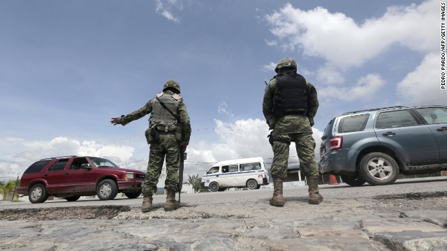 Mexican soldiers stand guard at a checkpoint in Iguala, Guerrero State, Mexico on September 29, 2014, following recent clashes that led to at least six deaths. Twenty two officers have been detained after the September 26 incident in the town of Iguala. Mexican prosecutors on Monday were investigating whether local police officers were involved in the disappearance of 57 students who vanished after deadly incidents in Guerrero state. AFP PHOTO/Pedro PARDO (Photo credit should read Pedro PARDO/AFP/Getty Images)