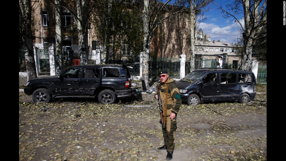 A pro-Russian rebel guards a damaged school in Donetsk on October 1.