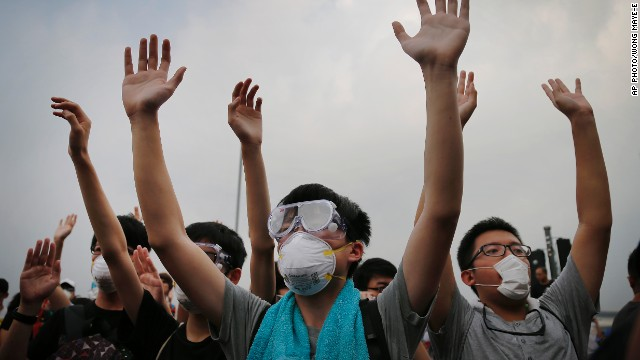 Student protesters raise their hands to show their non-violent intentions as they resist during change of shift for local police but backed down after being reassured they could reoccupy the pavement outside the government compound's gate, Thursday, Oct. 2, 2014 in Hong Kong.