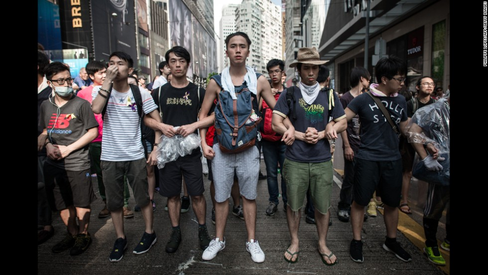 "Pro-democracy demonstrators protect a barricade from ""anti-Occupy"" crowds in Hong Kong on October 3."