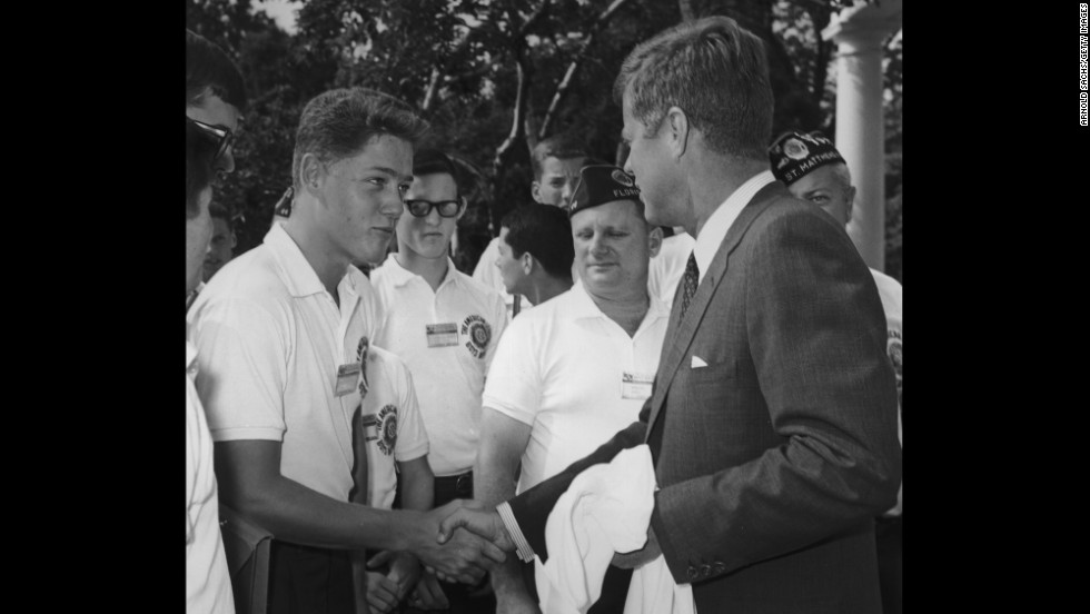 A young Clinton shakes hands with President John F. Kennedy while other American Legion Boys Nation delegates look on during a trip to the White House in 1963.