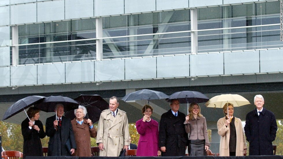 (From right) Clinton stands with his wife, daughter, President George W. Bush, Laura Bush, former President George H.W. Bush,  Barbara Bush, former President Jimmy Carter and Rosalynn Carter during the inauguration of the William J. Clinton Presidential Center in Little Rock, Arkansas, on November 18, 2004. The library and museum includes some 76.8 million pages of paper documents, 1.85 million photographs and over 75,000 artifacts from Clinton's eight years in the White House.