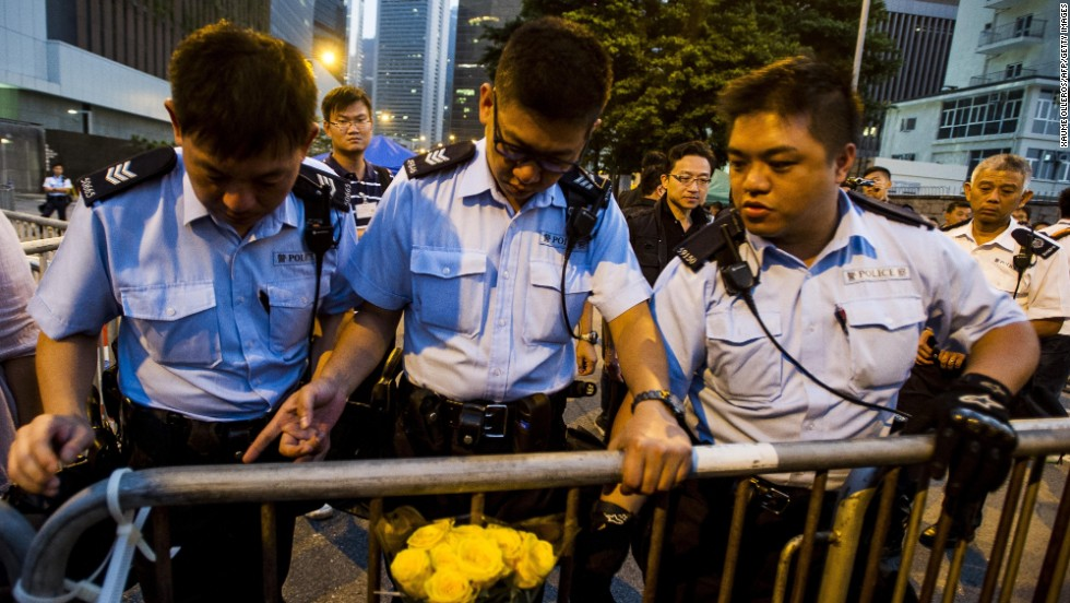 Police officers remove barriers outside government offices in Hong Kong on Sunday, October 5.
