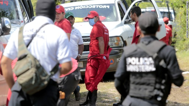 Mexican police officers and members of the civil protection remain in the site where a mass grave was found in Pueblo Viejo, in the outskirts of Iguala, Guerrero state, Mexico, on October 5, 2014. At least 21 bodies were pulled from a mass grave in southern Mexico and authorities checked Sunday if they were among a group of 43 students missing since a police shooting last week. AFP PHOTO/ Pedro PARDO (Photo credit should read Pedro PARDO/AFP/Getty Images)