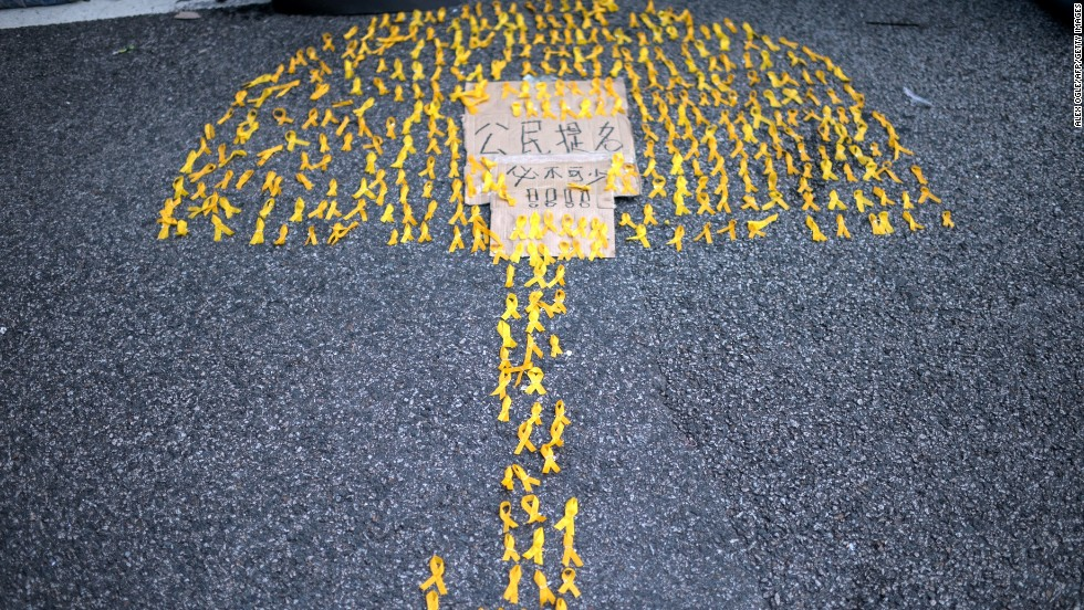 "An image of an umbrella made up of yellow ribbons is laid out on the ground near the central government offices. The sign reads: ""We can't live without civic nominations."""