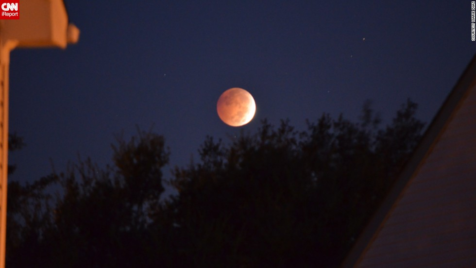 "The lunar eclipse hovers over <a href=""http://ireport.cnn.com/docs/DOC-1177442"">Marie Diaz's</a> home in Virginia Beach, Virginia, early Wednesday morning."