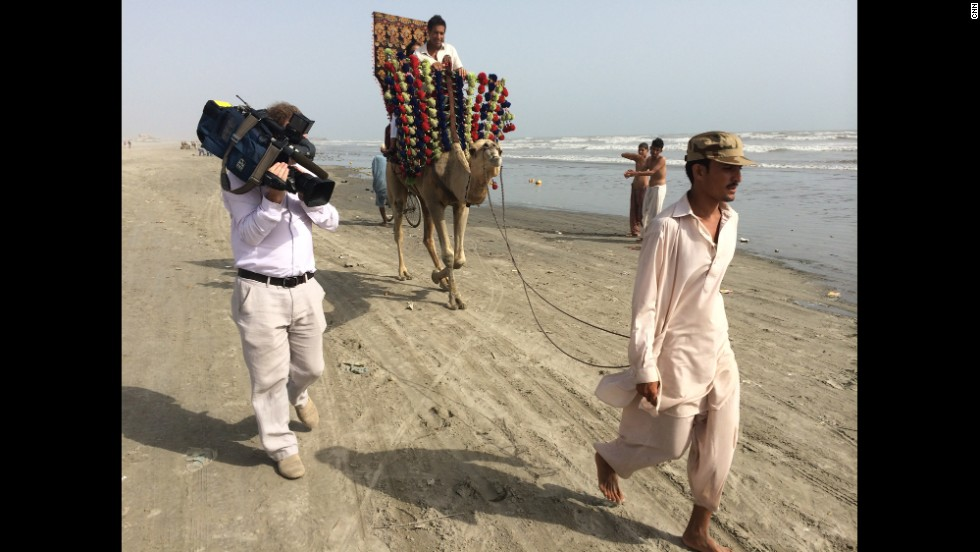 "Gupta rides a camel in Karachi, Pakistan. ""A beach. A camel. Karachi. Three things I never imagined going together,"" Gupta said. ""But it ended up becoming the beginning of our whole journey."""