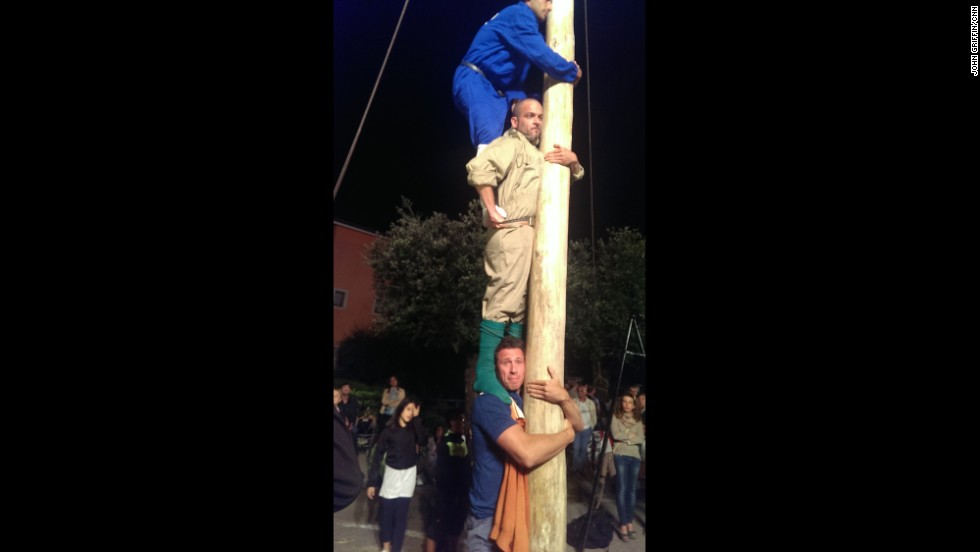 "Cuomo is the low man during a practice run for a ""Palo"" pole-climbing competition in Sant'Arsenio, Italy. The pole is greased with pig fat. It takes four men stacked on top of one another, and then the top man scampers up the pole to recover various goodies: prosciutto, cash and even cigarettes."