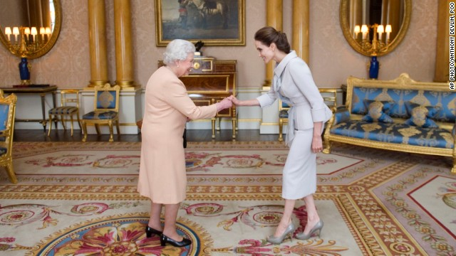 U.S actress Angelina Jolie, right, is presented with the Insignia of an Honorary Dame Grand Cross of the Most Distinguished Order of St Michael and St George by Britain's Queen Elizabeth II at Buckingham Palace, London, Friday, Oct. 10, 2014. Jolie received an honorary damehood (DCMG) for services to UK foreign policy and the campaign to end war zone sexual violence. (AP Photo/Anthony Devlin, pool)