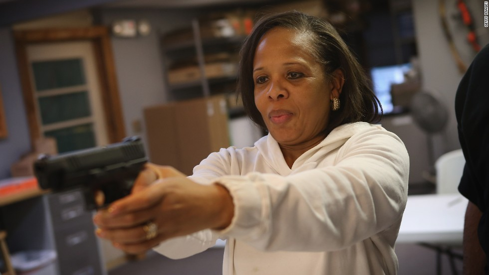 Cheryl Bourgeois learns how to fire a pistol during an NRA basic pistol course in Illinois. Historians say it's a mistake to think the American gun culture is lily white.