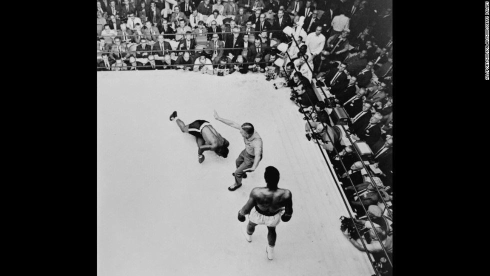 The referee pushes Ali to a neutral corner as Floyd Patterson slumps to the canvas in November 1965. The fight was stopped at the end of the 12th round and Ali was declared the winner.