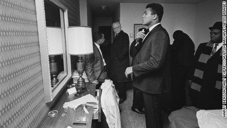 Ali looks in his hotel room mirror surrounded by members of his entourage on February 15, 1967.
