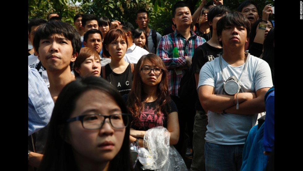 Pro-democracy protesters watch as police remove barricades on October 14.