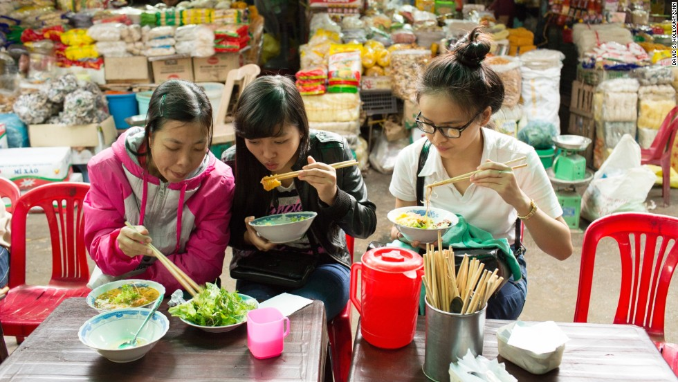 "Residents stop for bun bo Hue, an elaborate noodle soup, in Dong Ba Market. Bourdain calls it ""the greatest soup in the world."" Rice noodles are cooked and served in a spicy, rich broth made from beef and pork bones. It's often accompanied by cubes of congealed pork blood, banana blossoms, scallions and mung bean sprouts."