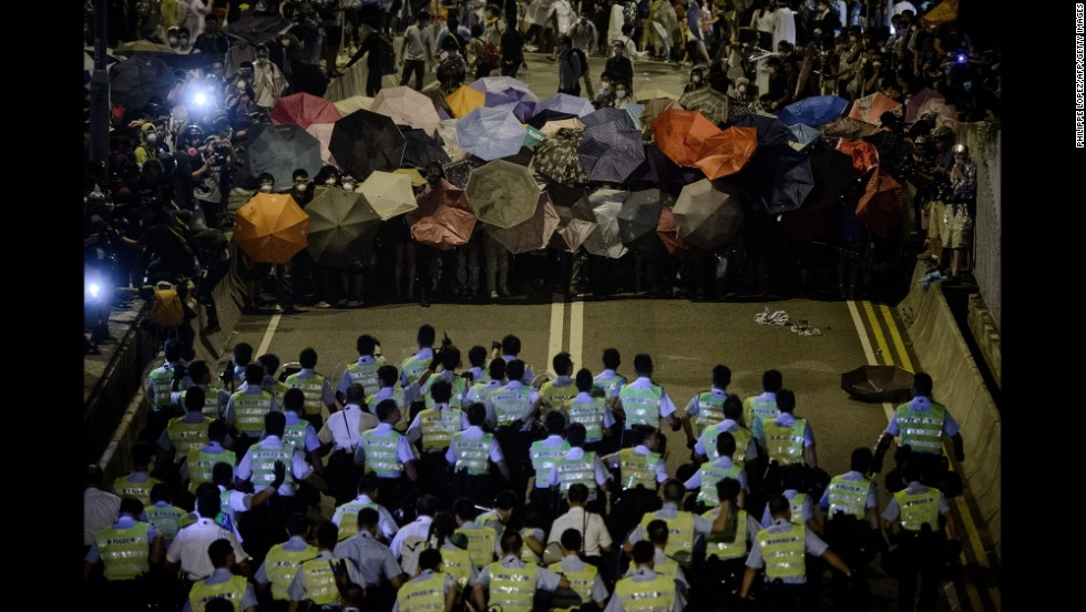 Police move toward pro-democracy protesters during a standoff outside central government offices on October 14.