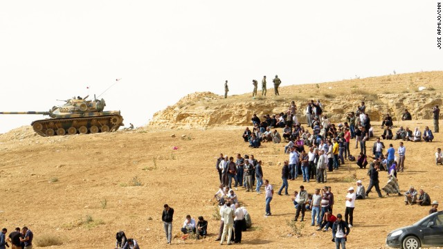 Kurdish people and Turkish soldiers watch fighting in the Syrian town of Kobani from a hilltop near the Turkish-Syrian border in this file photo.
