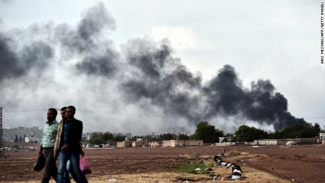 Kurdish men walks close to the Turkish-Syrian border as smoke rises from the Syrian town of Kobane, also known as Ain al-Arab, as seen from the southeastern village of Mursitpinar, in the Sanliurfa province, on October 16, 2014. Turkey's ruling party said it was optimistic about the prospects for the peace process with Kurdish rebels after a spate of violence raised concern about its viability. AFP PHOTO / ARIS MESSINIS (Photo credit should read ARIS MESSINIS/AFP/Getty Images)