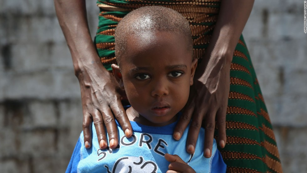 James Mulbah, 2, stands with his mother, Tamah Mulbah, 28, who also recovered from Ebola in the low-risk section of the Doctors Without Borders Ebola treatment center in Paynesville, Liberia.