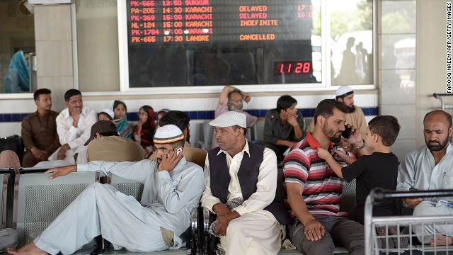 Passengers of Karachi-bound Pakistan International Airline (PIA) flights wait after delays at the Benazir Bhutto International Airport in Islamabad on June 9, 2014 following gunbattles in Karachi airport between militants and security forces. Twenty-eight people were killed as Pakistan's military fought an all-night battle Monday with Taliban gunmen who besieged Karachi airport armed with rocket launchers and suicide vests, leaving a nascent peace process in tatters. AFP PHOTO/Farooq NAEEM (Photo credit should read FAROOQ NAEEM/AFP/Getty Images)
