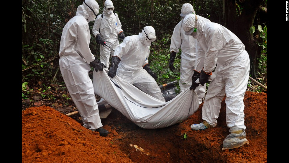 Health workers bury a body on the outskirts of Monrovia on October 20, 2014.