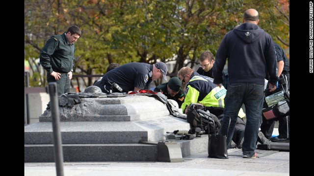 Emergency personnel tend to a soldier shot at the National War Memorial near Parliament Hill in Ottawa, Canada, on Wednesday, October 22.