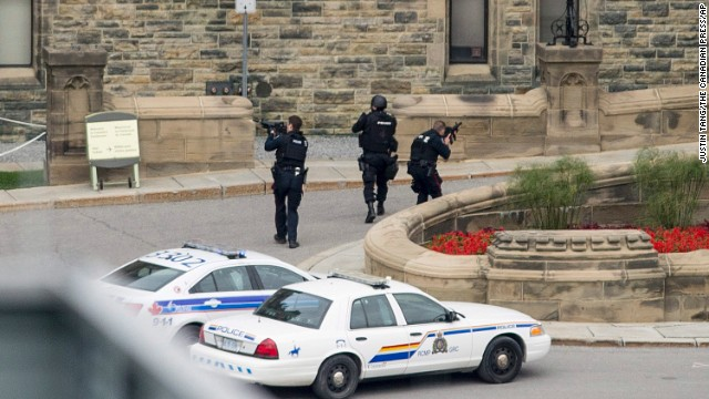Police teams enter Centre Block at Parliament Hill in Ottawa on  Wednesday Oct. 22, 2014.  A soldier standing guard at the National War Memorial was shot by an unknown gunman and people reported hearing gunfire inside the halls of Parliament. Prime Minister Stephen Harper was rushed away from Parliament Hill to an undisclosed location, according to officials. (AP Photo/The Canadian Press, Justin Tang/The Canadian Press/AP)