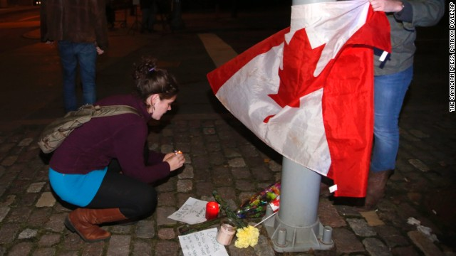 "Mourners light a candle and tie a Canadian flag around a light pole near the National War Memorial after a soldier was killed in Ottawa on Wednesday, Oct. 22, 2014. A gunman Wednesday fatally shot an honor guard at ""point blank"" range at the National War Memorial before storming Parliament Hill. (AP Photo/The Canadian Press, Patrick Doyle)"