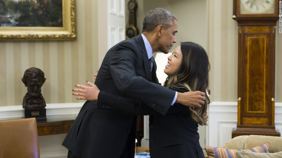 US President Barack Obama hugs nurse Nina Pham, who was declared free of the Ebola virus after contracting the disease while caring for a Liberian patient in Texas, during a meeting in the Oval Office of the White House in Washington, DC, October 24, 2014. AFP PHOTO / Saul LOEB (Photo credit should read SAUL LOEB/AFP/Getty Images)