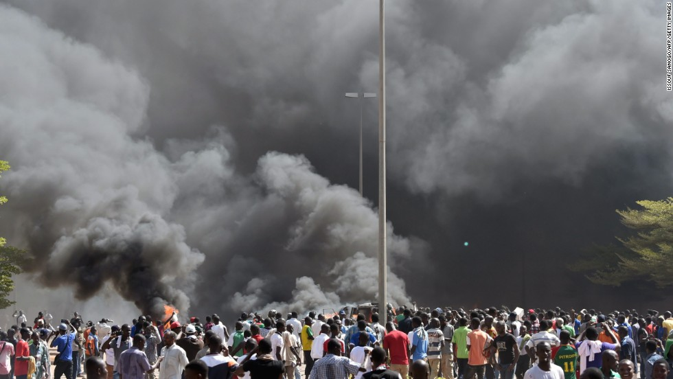 People stand in front of smoke rising from Burkina Faso's parliament building, where demonstrators set parked cars on fire Thursday, October 30.
